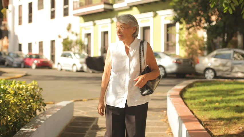 An older lady walks towards the camera in a park
