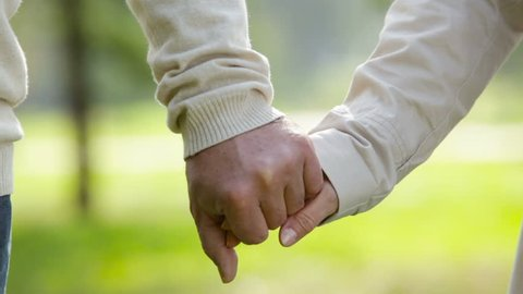 Close-up of an elderly couple holding hands and walking together