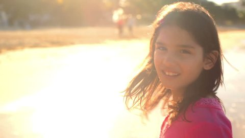 A young girl plays at the water's edge with the sun behind her at the beach and smiles into the camera