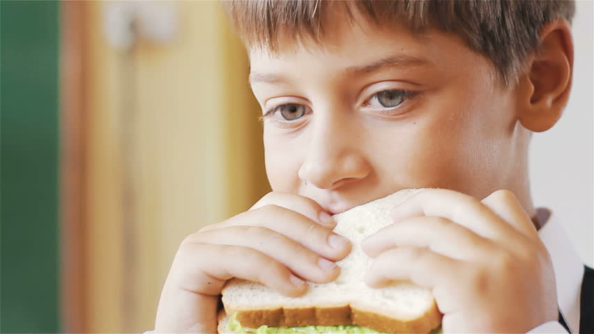 Little schoolboy eating sandwich in class