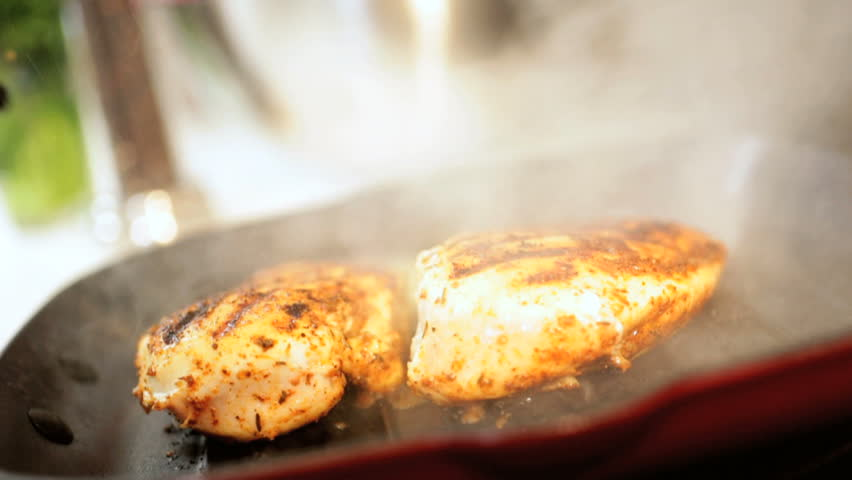 Healthy marinated chicken cutlets grilling on a griddle pan close up view