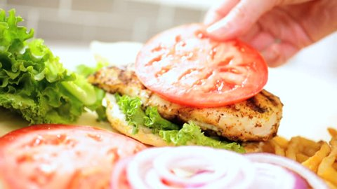 Close up of a delicious grilled chicken breast sandwich being assembled with crunchy lettuce, tomato, and onion