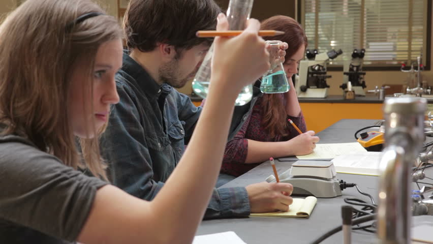 Students do work and experiments during a college lecture