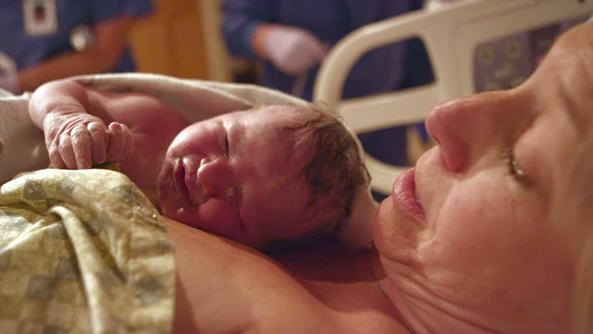 A mother holds her new born after giving birth