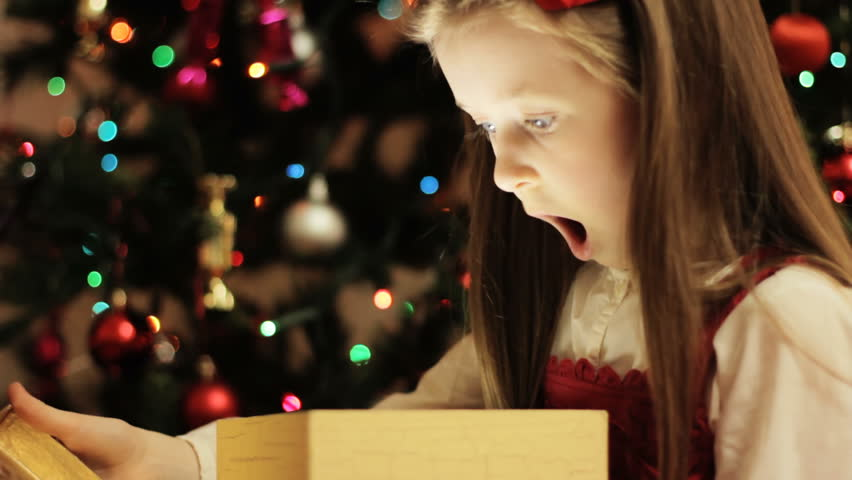 Christmas gift surprise - A little girl opens a Christmas present in amazement