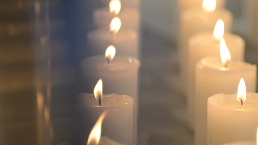 Dolly Shot Of White Candles Burning Aligned In Vertical Lines.