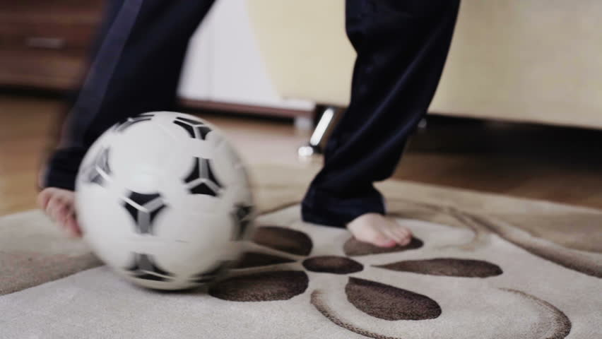 close up of young european boy playing with a soccer football at home in the living room