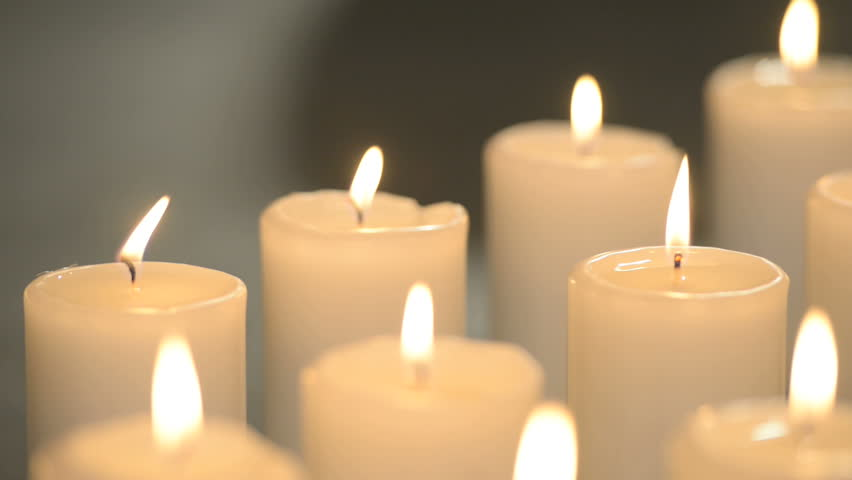 Dolly Shot Of White Candles Burning With Soft Candle Light On Black Background