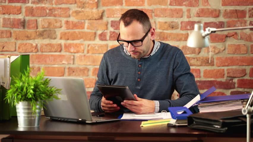 Multitasking young man working in modern office
