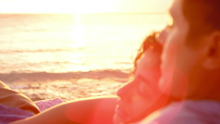 A woman lays on a man's chest as they sit on the beach and watch the sun set together | Shutterstock Video #4776395