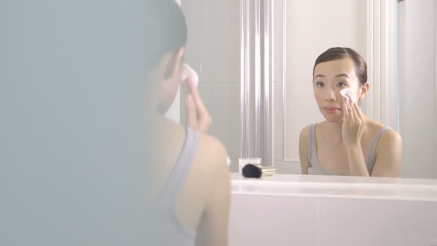 MS PAN Young woman using face cleanser and removing make-up