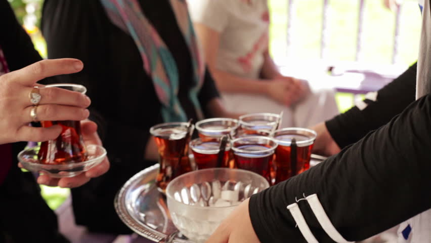 person serving tea on a silver plate with sugar cubes and teaspoons to guests outside of a house during the day