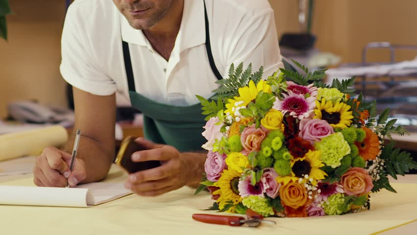 portrait of mid adult man working as florist in flower shop, taking order from client by phone