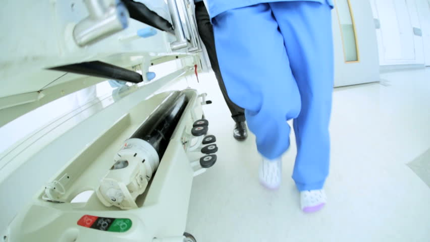 Medical staff wheels elderly patient on hospital bed through corridor towards operating room low angle slow motion view