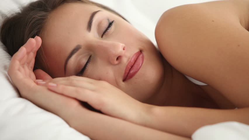 Cute young woman sleeping in bed waking up and smiling at camera. Panning camera