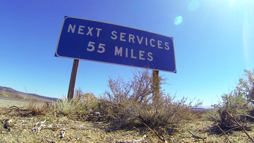 A sign on a lonely desert road warns that the next services are 55 miles away.