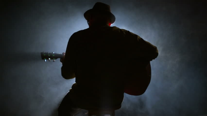 A silhouette of a guitar player sitting on a stool