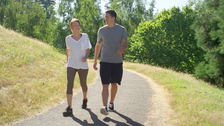 Fit and healthy young couple walks through the park | Shutterstock HD Video #4867337