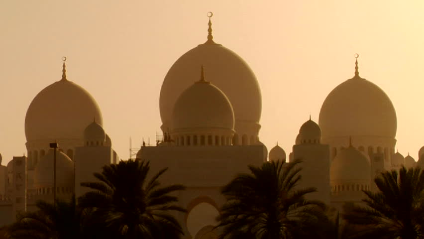 The domes of the beautiful Sheikh Zayed Mosque in Abu Dhabi, United Arab Emirates at sunset.