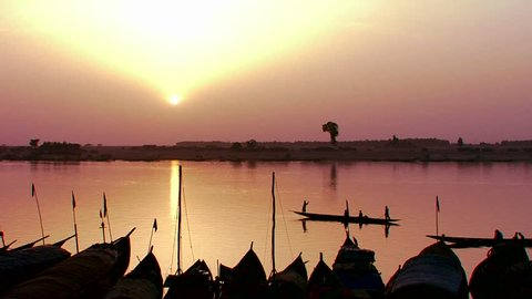 Fishermen row at sunset on the Niger River in beautiful golden light in Mali, Africa.