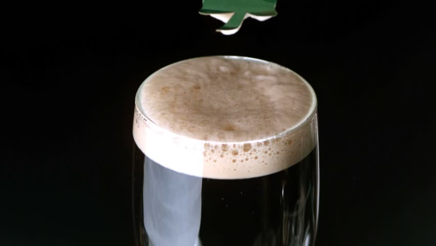 Shamrock landing on head of pint of stout on black background in slow motion