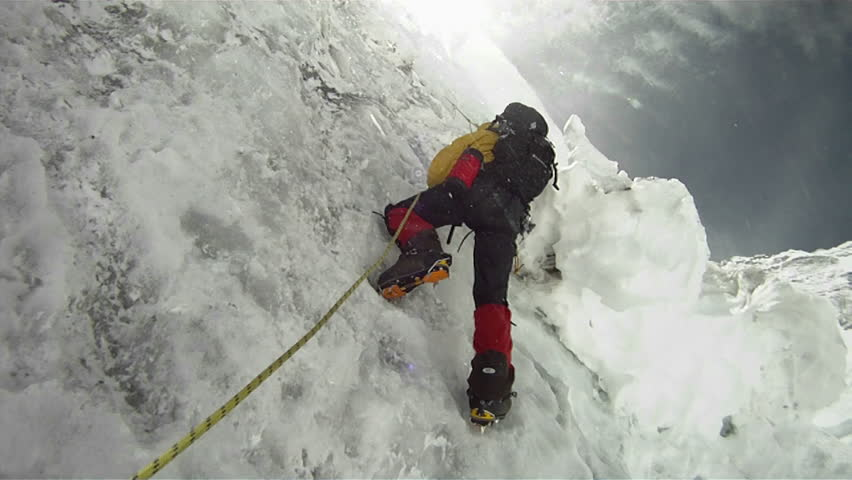 Climber on icy wall with wind and snow blowing