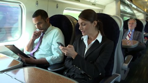Businessman using digital tablet while female colleague talks on mobile phone on commuter train