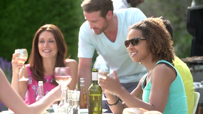 Young adult friends eating and drinking together in summertime