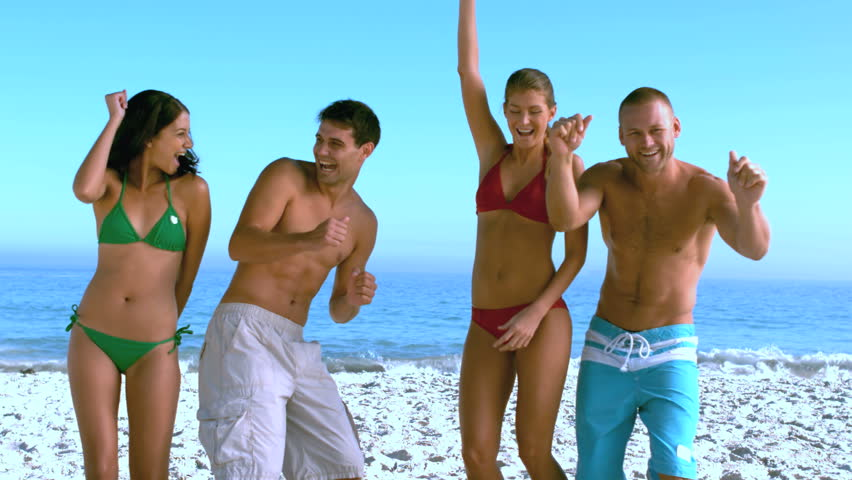 Group of friends dancing on the beach in slow motion