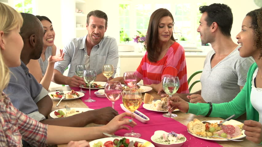Group of young adults toasting glasses together and drinking at dinner party