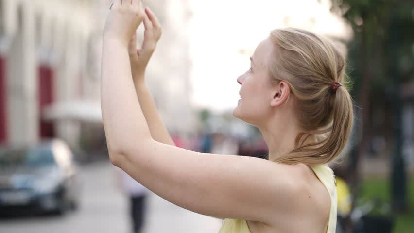 Beautiful young blond woman taking a photo while sightseeing looking up with an expectant smile at something off frame
