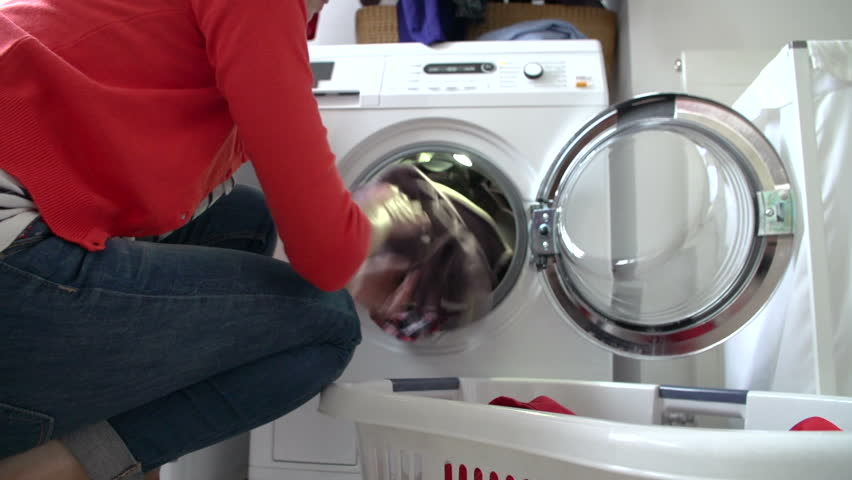Middle aged woman loads washing machine from laundry basket and turns on machine