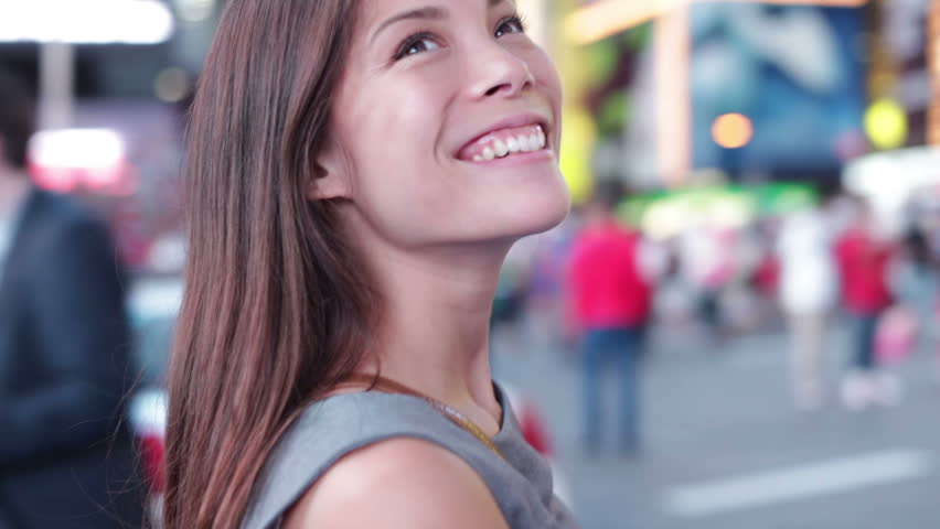 Business woman looking around and walking on Times Square, New York City at night. Beautiful young multiracial businesswoman on Manhattan, USA. Asian Caucasian mixed race woman.