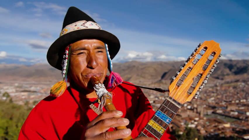 CUSCO, PERU - CIRCA 2010: Traditional musician , Cusco in background