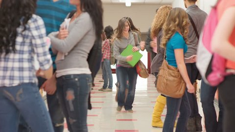 Students run after each other through the hallway full of other kids waiting for class to start