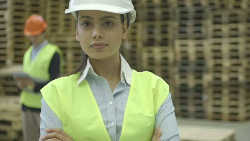 CU TU Female engineer standing and male engineer using digital tablet in background