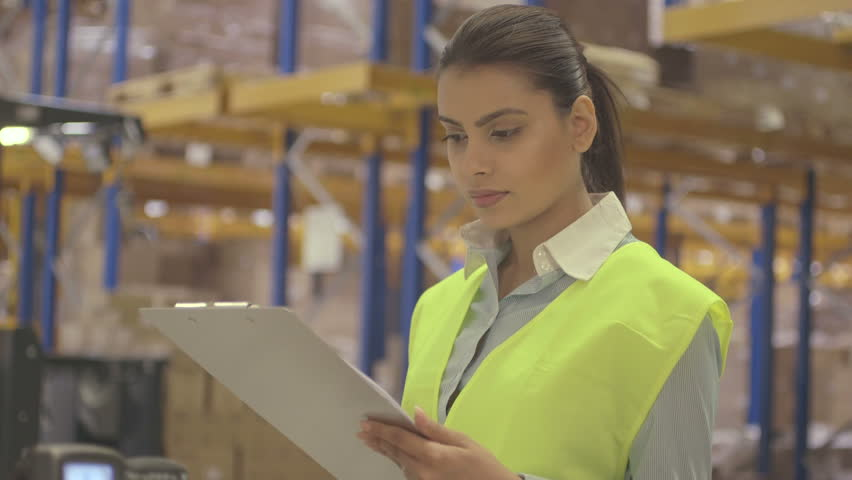 MS Young woman engineer standing and holding clipboard in factory warehouse