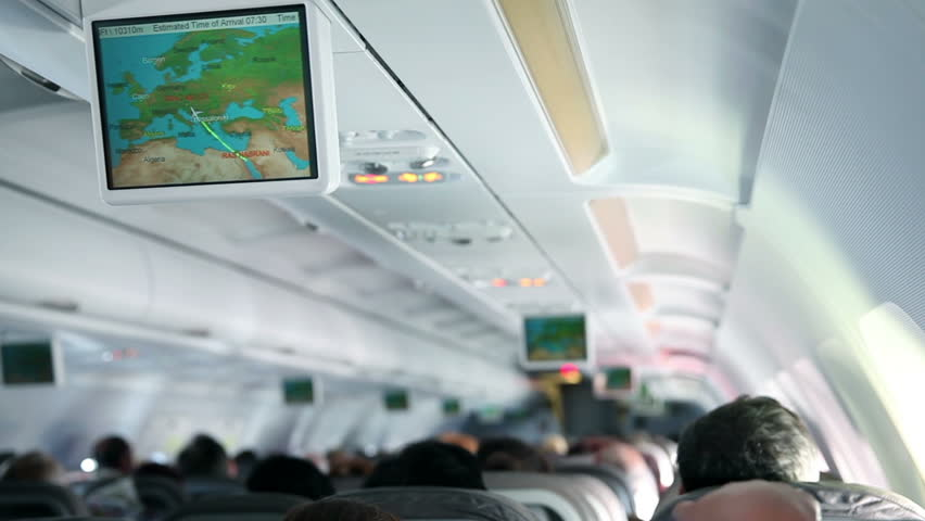 Airplane passenger cabin with people watching television screens