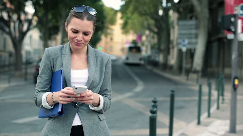Businesswoman with smartphone standing by city street  | Shutterstock HD Video #4912454