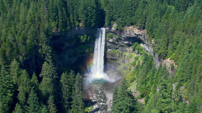 Helicopter shot of a big waterfall in British Columbia. Sunlight and a rainbow from the spray.