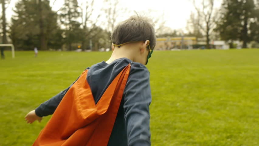 Superhero Boy Runs Around Park Pretending To Fly