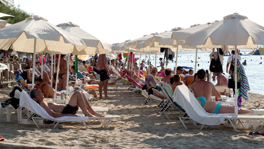 THESSALONIKI, GREECE - AUGUST 23: Crowded summer beach at a tropical resort with beachgoers relaxing under beach umbrellas on the golden sand on August 23, 2013 in Thessaloniki, Greece