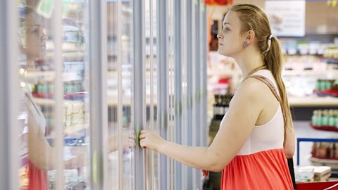 Young woman buying dairy or refrigerated groceries at the supermarket in the refrigerated section opening glass door of the fridge