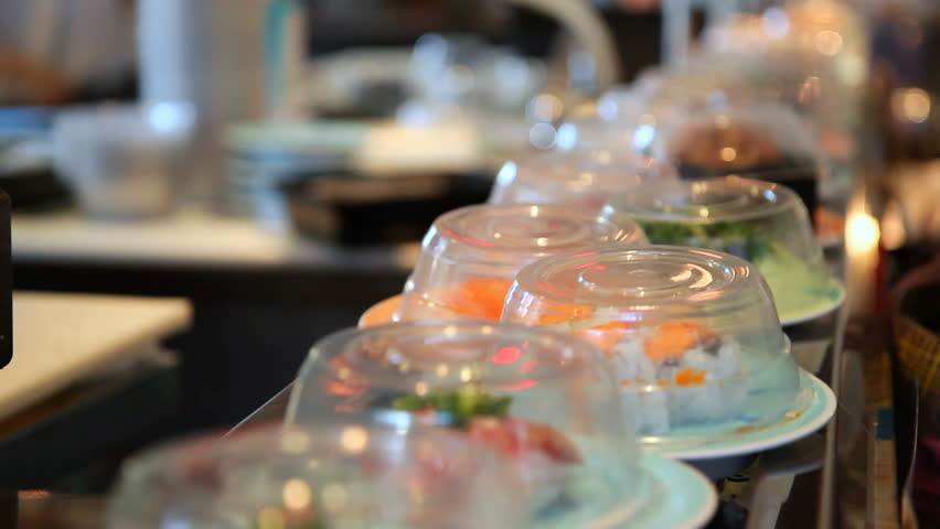 Sushi going past on conveyor belt. Shallow depth of field. Blurred movement in the background.
