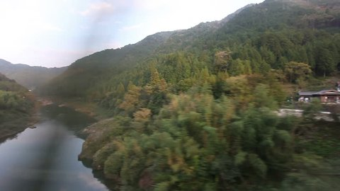 JAPAN - 30 OCTOBER 2013: A JR train rides through mountain and Countryside as seen from inside through a window in between Takayama and Nagoya pov