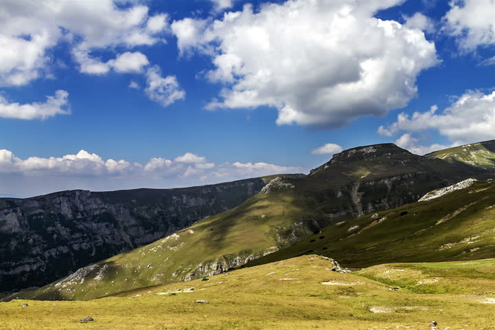 Romania mountains landscape time lapse 2K. Transylvania Romania mountains landscape time lapse. Fast motion. Clouds are moving close to the mountain top. Green meadows and trees, blue sky.