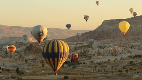 GOREME - OCTOBER 13: Lots of hot air balloons flying over valleys on October 13, 2013 in Goreme, Turkey. Tourists from all over the world come to Cappadocia to make a trip in a hot-air balloons.