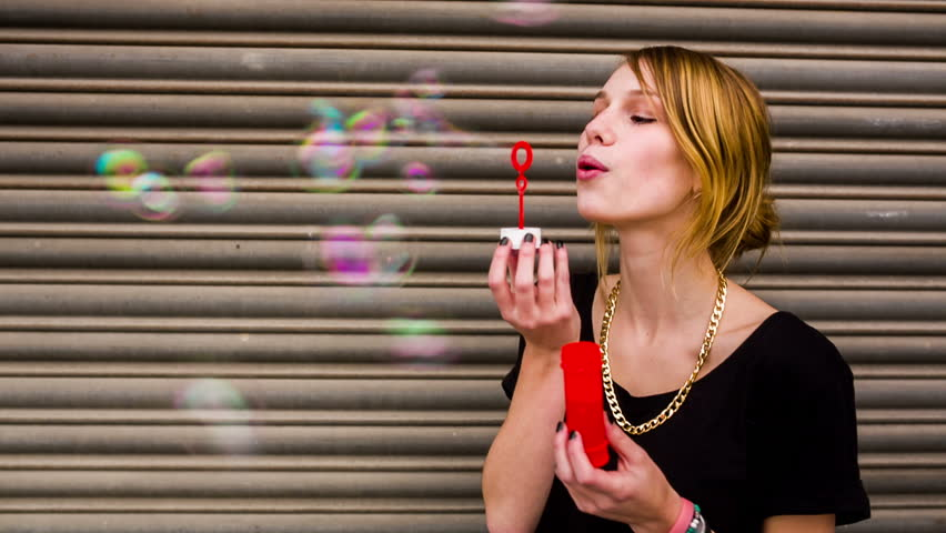 Young hipster girl having fun blowing bubbles