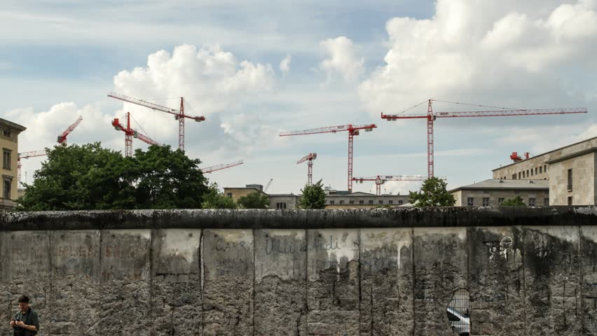 A large group of red building cranes near the Berlin Wall. A common sign of the rapidly changing face of the capital city of Germany.