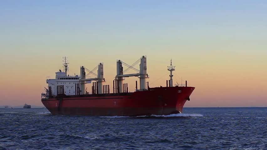 Cargo ship sailing from open sea. A bulk carrier ship with deck cranes on the sunset time.